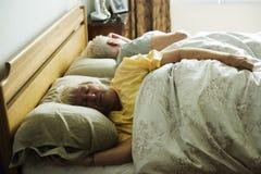 Couples caucasiens pluss âgé dormant sur le lit Images stock