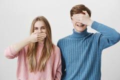 Couples caucasiens positifs de sourire se tenant près de l'un l'autre contre le mur gris Bouche de dissimulation de fille blonde  Images stock