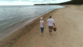 Couples caucasiens retirés le week-end marchant sur la plage ensemble banque de vidéos