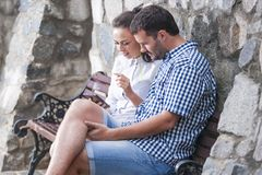Couples caucasiens se reposant ainsi que Smartphone et écoutant la musique Photographie stock libre de droits