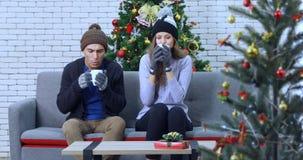 Couples caucasiens se reposant parmi l'arbre de Noël banque de vidéos