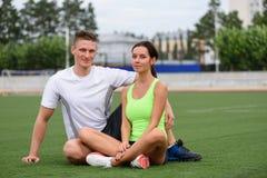 Couples caucasiens se reposant sur la pelouse après forme physique Photographie stock