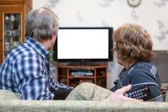 Couples caucasiens supérieurs se reposant devant la TV et l'écran blanc d'isolement de observation Images stock