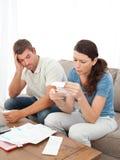 Couples chargés faisant leurs comptes Images stock
