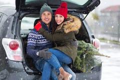 Couples chargeant l'arbre de Noël fraîchement réduit dans le dos de leur voiture Photographie stock libre de droits