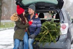 Couples chargeant l'arbre de Noël fraîchement réduit dans le dos de leur voiture Photo stock