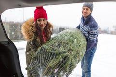 Couples chargeant l'arbre de Noël fraîchement réduit dans le dos de leur voiture Photos stock
