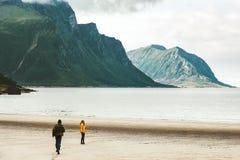 Couples chez l'homme d'amour courant à la femme au mode de vie heureux d'émotions de voyage de plage de la Norvège de mer Photos libres de droits