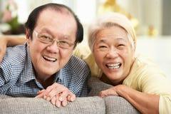 Couples chinois aînés détendant sur le sofa à la maison Photographie stock