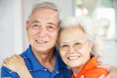 Couples chinois aînés détendant sur le sofa à la maison Photographie stock libre de droits