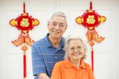 Couples chinois aînés en dehors de maison avec Feng Shui Photos stock