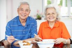 Couples chinois aînés se reposant à la maison mangeant le repas Photographie stock libre de droits