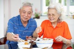 Couples chinois aînés se reposant à la maison mangeant le repas Image stock