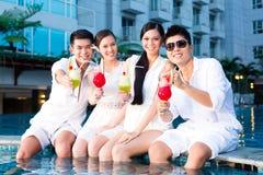 Couples chinois buvant des cocktails dans la barre de piscine d'hôtel Photographie stock