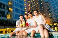 Couples chinois buvant des cocktails dans la barre de piscine d'hôtel Photo libre de droits