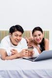 Couples chinois faisant des emplettes en ligne de leur chambre à coucher Photographie stock