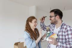 Couples choisissant des couleurs pour l'appartement de peinture photographie stock libre de droits