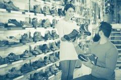 Couples choisissant des espadrilles dans le magasin Images libres de droits