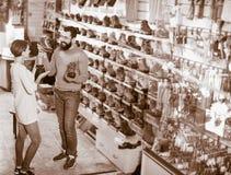 Couples choisissant des espadrilles dans le magasin Photographie stock