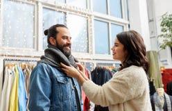 Couples choisissant des vêtements au magasin d'habillement de vintage Photos stock