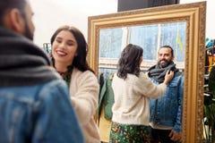 Couples choisissant des vêtements au magasin d'habillement de vintage Photo libre de droits