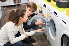 Couples choisissant la machine à laver dans l'hypermarché et le sourire Images libres de droits