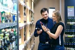 Couples choisissant le vin de stock de bouteille Photos stock