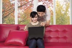 Couples choisissant quelque chose sur l'ordinateur portable Image stock