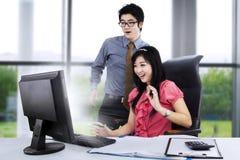 Couples choqués devant l'ordinateur Photo stock