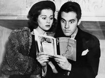 Couples choqués lisant ensemble (toutes les personnes représentées ne sont pas plus long vivantes et aucun domaine n'existe Garan Photographie stock
