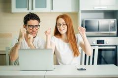 Couples choqués observant quelque chose sur l'ordinateur portable à la maison Photo libre de droits