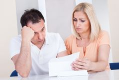 Couples choqués regardant la facture Image libre de droits