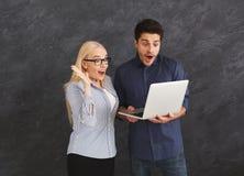 Couples choqués utilisant l'ordinateur portable au studio Photos libres de droits
