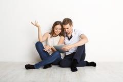 Couples choqués utilisant l'ordinateur portable, se reposant sur le plancher Photos stock