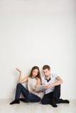Couples choqués utilisant l'ordinateur portable, se reposant sur le plancher Images libres de droits