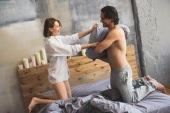 Couples combattant ainsi que des oreillers dans le lit Images stock