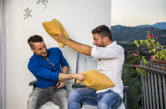 Couples combattant avec des oreillers sur le balcon Images libres de droits