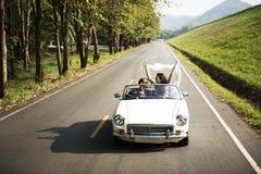 Couples conduisant une voiture voyageant sur le voyage par la route ensemble photos libres de droits