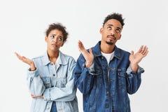 Couples confus dans des chemises de denim se tenant ensemble et recherchant Photographie stock libre de droits