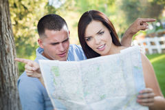 Couples confus de métis regardant au-dessus de la carte dehors Photographie stock libre de droits