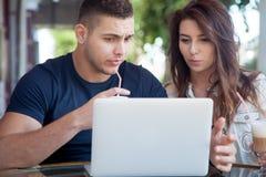 Couples confus regardant l'ordinateur portable un café Images libres de droits