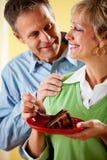 Couples : Consommation d'un morceau de gâteau de chocolat Photographie stock libre de droits