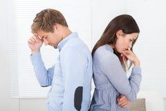 Couples contrariés se tenant de nouveau au dos à la maison Photographie stock libre de droits