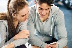 Couples convenables dans le gymnase moderne de crossfit avec le smartphone Photographie stock libre de droits