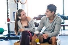 Couples convenables de beaux jeunes dans parler moderne de gymnase de crossfit Photographie stock