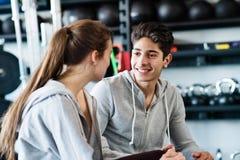 Couples convenables de beaux jeunes dans parler moderne de gymnase de crossfit Photos stock