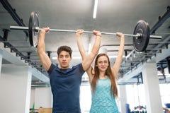 Couples convenables de jeunes dans le gymnase soulevant le barbell lourd Photo stock