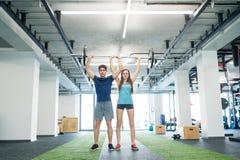 Couples convenables de jeunes dans le gymnase soulevant le barbell lourd Photo libre de droits