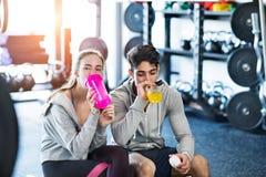 Couples convenables de jeunes en eau potable de gymnase moderne de crossfit Image stock