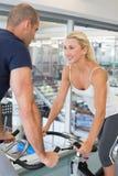 Couples convenables de sourire travaillant aux vélos d'exercice au gymnase image stock